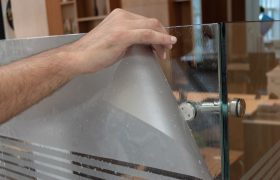 Mužská ruka provádí výlep folie na skleněnou příčku v kanceláři