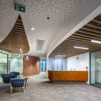 Designová chodba, modrobílá abstraktní fototapeta na stěně za recepčním pultem, modrá křesla, sloup, dřevěné příčky na stropě s visícími žárovkami, šedá podlaha