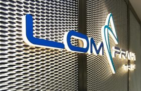 Modré světelné 3D logo LOM Praha Trade, montáž na tahokov