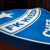 Modrý světelný panel tvaru erbu, s bílými nápisy a detaily ohledně klubu shora, vyfocený ležící z levého boku, na hnědém podkladu