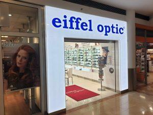 Světelná vstupní brána do obchodu eiffel optic, bílý rám, modrá svítící plexi písmena