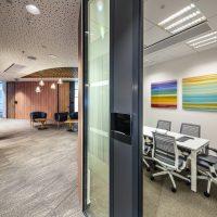 Designová chodba, hnědá fototapeta na stěně s motivem dřeva, barevné duhové obrazy na bílé stěně, konferenční stůl, kancelářské židle, skleněná příčka, modrá křesla, dřevěné stolky