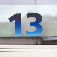 Modrá plotrovaná číslice 13 na skleněné výplni, označení čísla vchodu O2 Universum