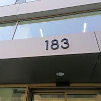 3D označení popisného čísla administrační budovy 183, černé plexi lepené na fasádě mezi vchodem a oknem prvního patra