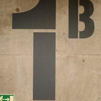 Šedý malovaný nápis 1B na betonové stěně, označení únikového východu