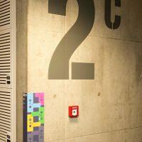 Malované označení 2C na betonové stěně, barevný plánek budovy, požární hlásič