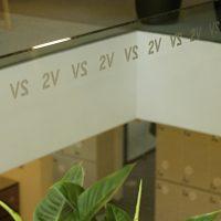 Dekorativní označení opakujícím se nápisem 2V, plotrový polep na skleněné přepážce