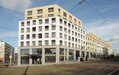 Pohled na ubytovací zařízení Student House v Praze, šedo bílo žlutá fasáda, na pozadí obloha s mraky