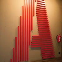 Velké písmeno A složené z červených kovových hranolů, lepené na zdi