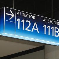 Světelná navigační stropní výstrč na dvou kovových závěsech, modrý box s šipkou označující směr k sektorům A1 112A a 111B