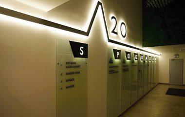 Světelná lišta a číslo 20 na bílé stěně, skleněné orientační tabule