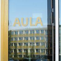 Zlatý nápis AULA na okenní tabulce, zrcadlový odraz budovy ČZU v Praze