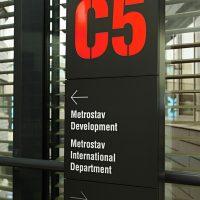 Černý informační totem, červené značení C5, bílé nápisy Metrostav Development, Metrostav International Department, divize 5, šipky