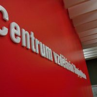 Bílý 3D nápis Centrum vzdělávání, rozostřené pozadí, červená zeď