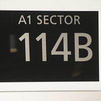 Černá informační tabule s gravírovaným stříbrným textem A1 SECTOR a označením 114B