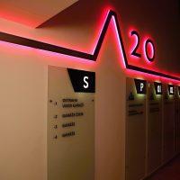 Červeně podsvícená lišta, světelný nápis 20, podsvícené informační tabule s čísly pater, frézované nápisy