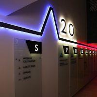 Modro-bílo-červeně podsvícená lišta na stěně, světelný nápis 20, skleněné informační tabule