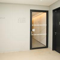 Šedé navigační piktogramy v kroužku na bílé stěně chodby, bílý piktogram obálky v kroužku na černých dveřích