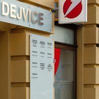 3D nápis DEJVICE na mléčném skle nad vchodem do budovy ordinace, informační deska vedle vchodu a světelná výstrč s logem UniCredit Bank