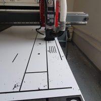 Bílá dibondová deska s černým jádrem na CNC fréze, frézované drážky