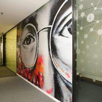 Fototapeta s motivem Johna Lenonna na zdi, výzdoba chodby, polep skleněných příček s motivem kruhů a přímek