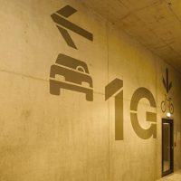 Malovaná grafika na betonové stěně garáže, symbol auta s šipkou, nápis 1G, symbol jízdního kola s šipkou
