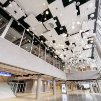 Vstupní lobby O2 Universum, mnoho bílých deskových podhledů a závěsných kulových svítidel, schodiště s modrou stropní výstrčí