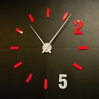Moderní nástěnné hodiny na černé stěně, červené čárky a číslice 2, bílé hodinové ručičky a číslice 5