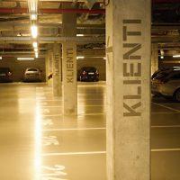 Podzemní garáž, malované nápisy KLIENTI a šipky na sloupech, značení parkovacích míst na zemi