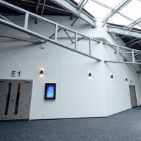 Chodba pod střešní konstrukcí O2 Universum, šedé nosníky kotvené do zdi, šedé dvoukřídlé dveře s 3D označením E1