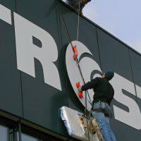 Montáž bílého loga Metrostav na plášť budovy, technik na žebříku, jištění na oranžová přísavná madla