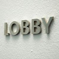 Hliníkový 3D nápis LOBBY nalepený na bílé strukturované zdi