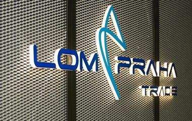 Světelné modro bílé 3D logo LOM Praha na černé děrované plechové příčce z tahokovu