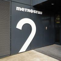 Bílé logo Metrostav, horní část písmena 2, černý plášť budovy
