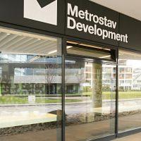 Bílé logo Metrostav Development na černém plášti nad skleněnou stěnou, výhled ven z budovy