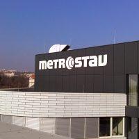Bílé logo Metrostav lepené na černém plášti vrchní části budovy
