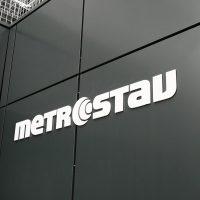 Bílé logo Metrostav lepené na černém plášti budovy, pohled zespoda