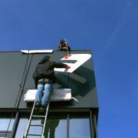 Montáž loga, lepení bílých frézovaných písmen na plášť budovy, technici na žebříku