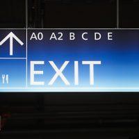 Světelná navigační stropní výstrč, modrý box, bílý nápis EXIT, označení sektorů, šipka nahoru a piktogram příbor