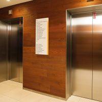 Bílá deska s oranžovou hranou a černým značením směrů na hnědém dřevěném obložení zdi mezi nerezovými dveřmi výtahů