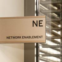 Šedá informační výstrč na zdi, černé označení NE NETWORK ENABLEMENT, skleněné okno s žaluziemi