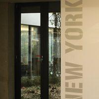 Svislý malovaný nápis NEW YORK na stěně chodby administrační budovy, skleněné dveře
