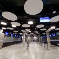 Food court v O2 Universum, šedá podlaha, sloupy a obložení stěn, podhledy z množství bílých kruhů, dvě řady vysokých stolků