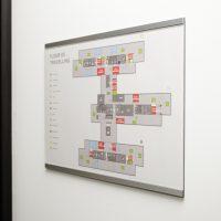 Orientační plán na skleněné desce, označení FLOOR 05 TRAVELLING, bílá zeď