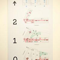 Orientační plán budovy, bílá deska na stěně, černá čísla 0, 1, 2 a šipka, barevné plány jednotlivých pater