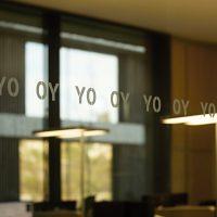 Skleněná příčka s opakovaným plotrovým značením písmeny OY v řadě