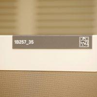 Hliníkový štítek s označením pracovního místa, černý nápise a QR kód, paravan z béžové textilie