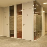 Plotrovaná pískovaná folie na skleněné příčce, motiv jedničky a nuly, bílé dveře s piktogramem