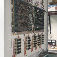 Elektrické spoje a komponenty na zadní straně bílého dibondového boxu na zeleném pracovním stole