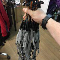 Ruka držící svazek barevných kabelů s černými konektory